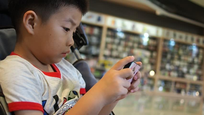 bambino giapponese impegnato con i videogiochi